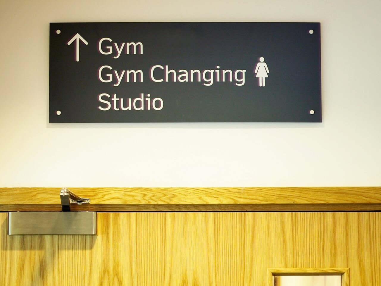 Directional signage and information graphics are positioned above doors for added visibility in busy public spaces like gym facilities