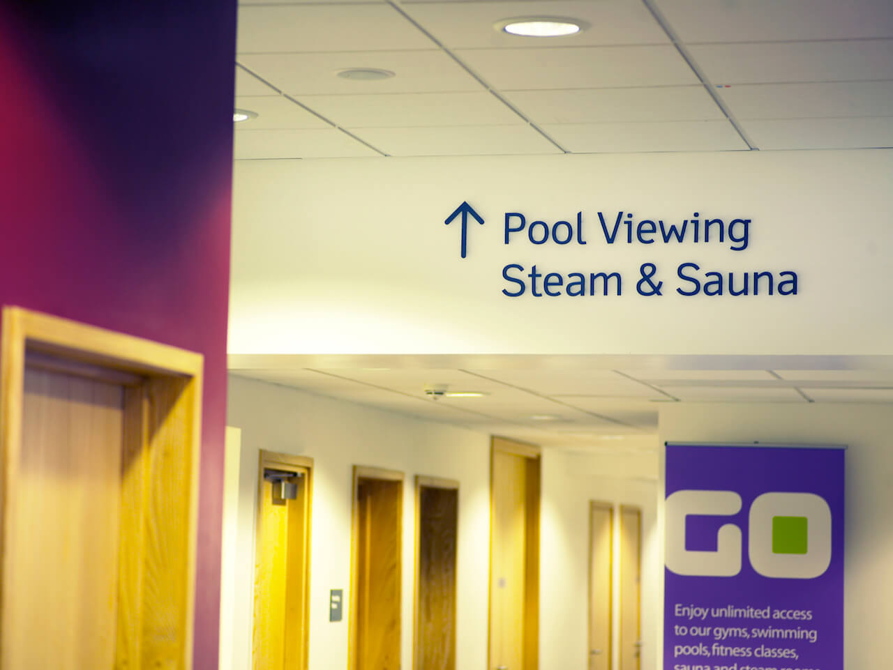 Clear signage and information graphics indicate areas within a swimming pool facility