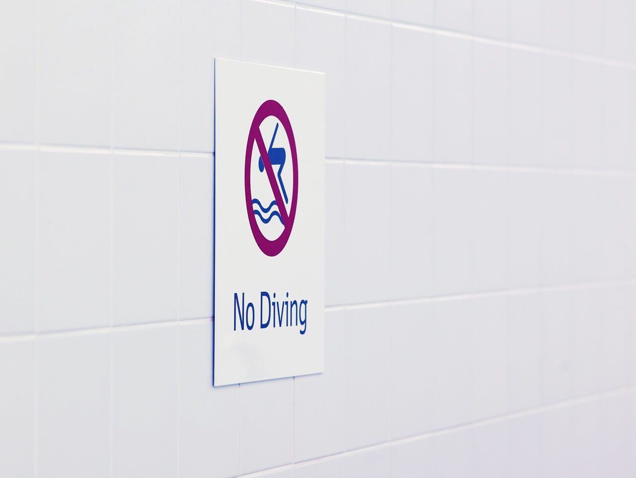 Wayfinding and signage in pool areas indicates no diving, using robust chlorine-proof materials