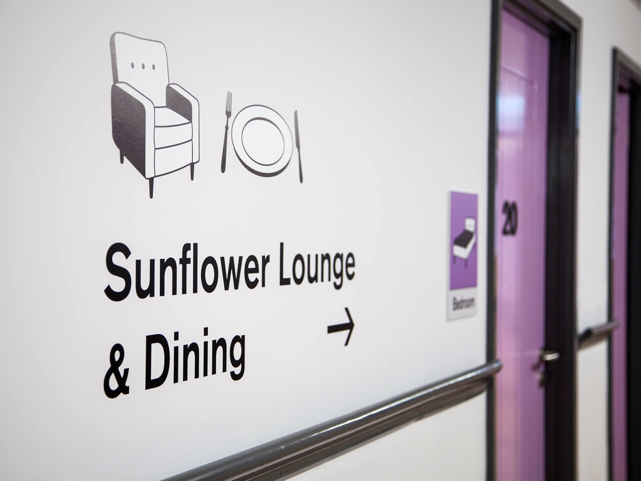 Wall graphics with dementia friendly directional signs at Haven Court