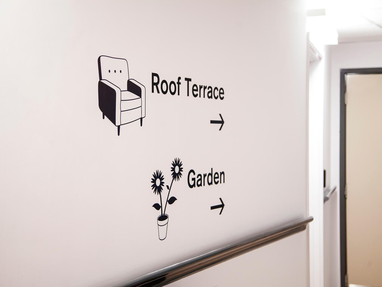 Pictograms and directional signage at Haven Court in a wayfinding scheme for people living with dementia