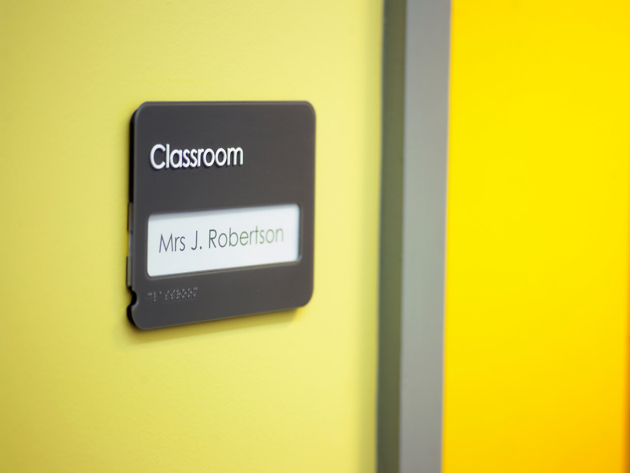 Classroom signage with paper inserts and Braille