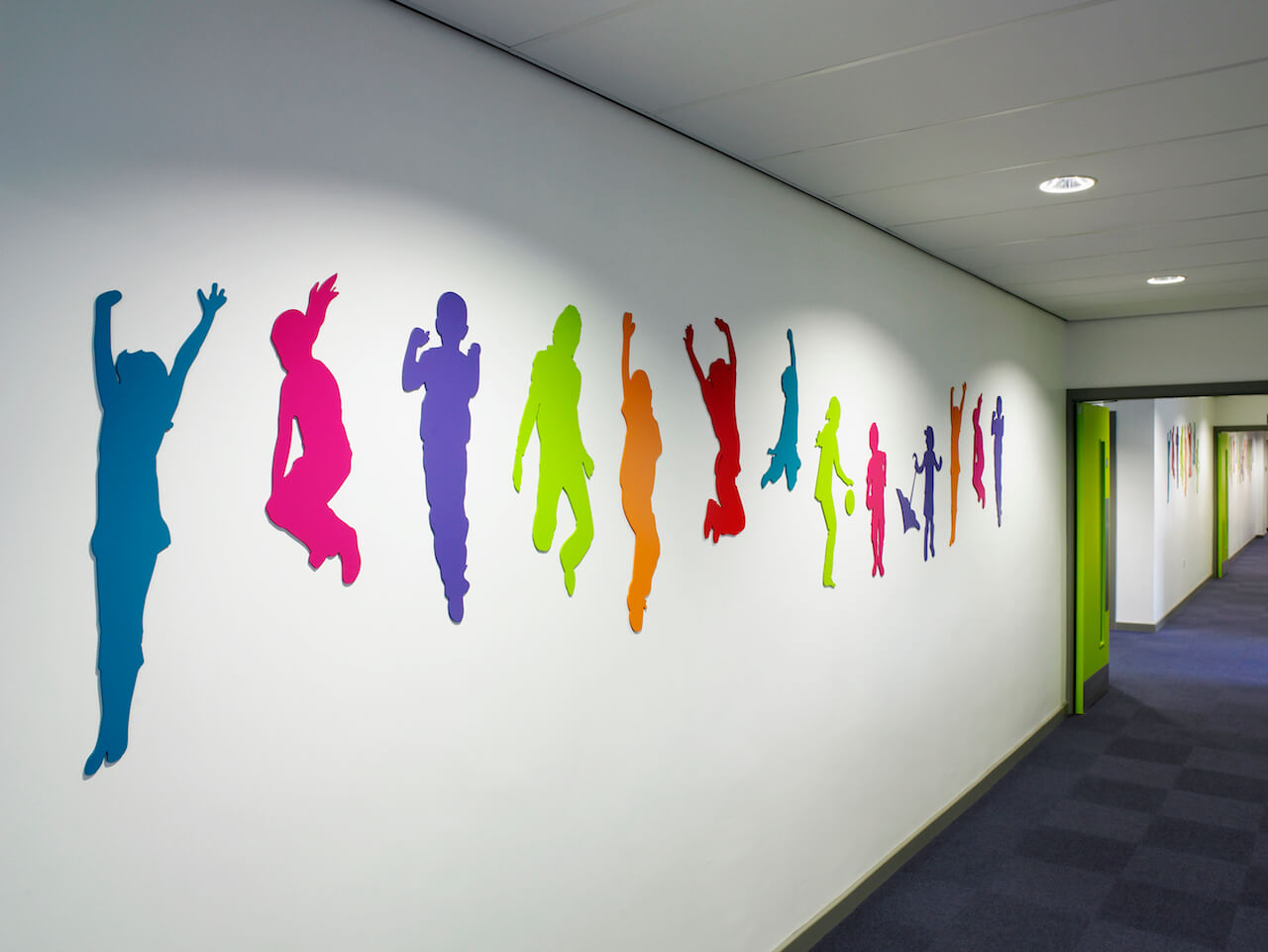 Wayfinding and environmental graphic design with a multi-coloured supergraphic of children jumping