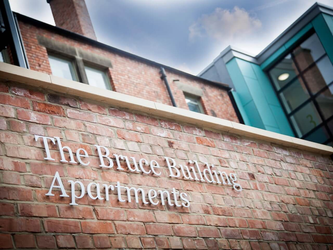 The Bruce Building Apartments name sign on an external brick wall in white letters