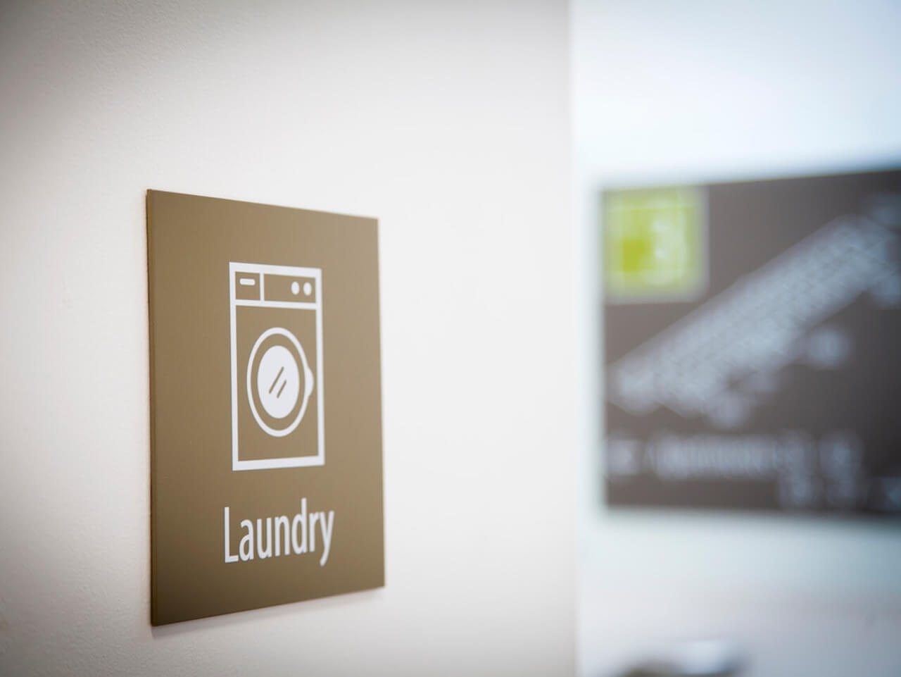 A wayfinding sign with a washing machine icon to show the laundry room