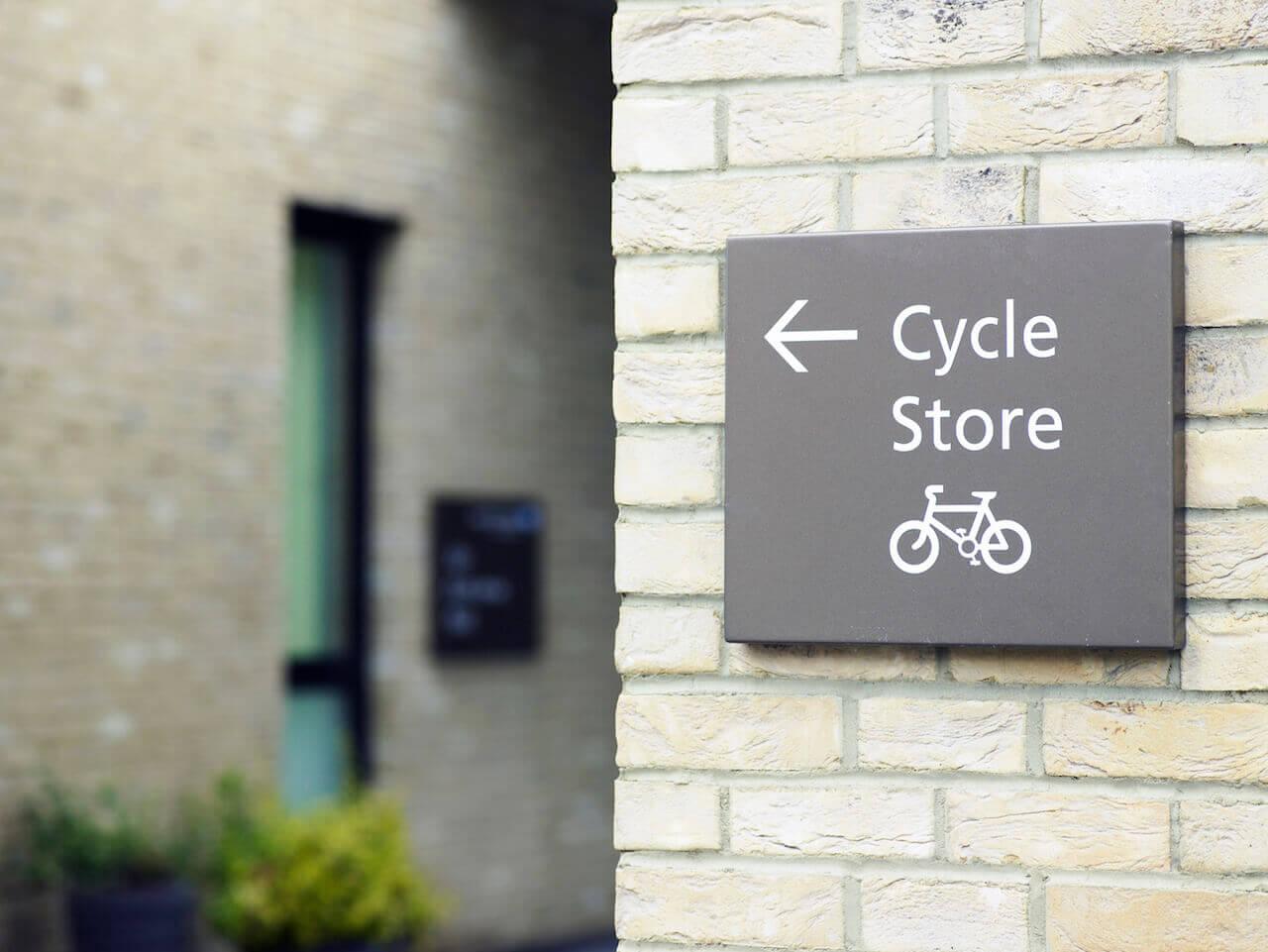 An external wall sign with a cycle logo showing the directions to the cycle store