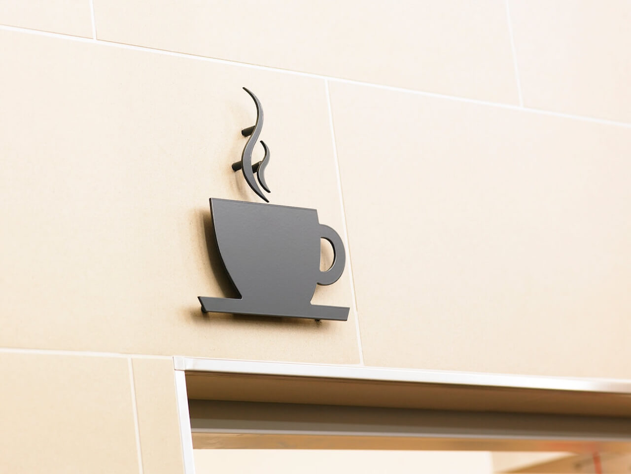 A coffee cup with steam plaque above a doorway depicting the entrance to the café