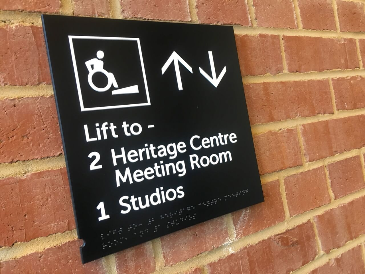 A black wayfinding site showing ramp wheelchair access to locations in the building