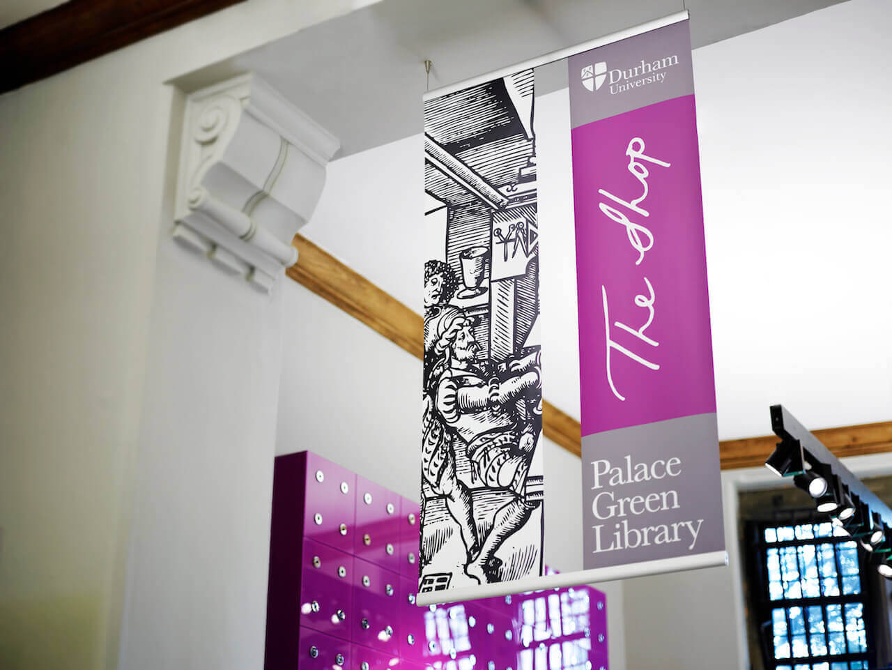 Shop detail banners suspended from the ceilings at Palace Green Library