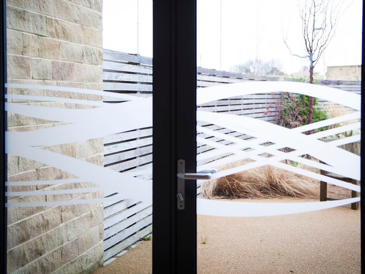 Detail of wave motif window manifestation across opening doors to garden