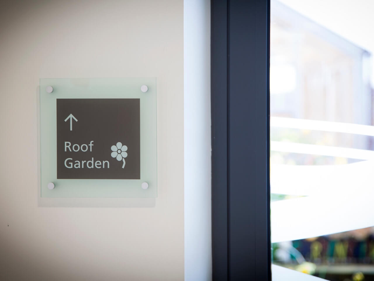 Wall mounted signage with floral pictogram to a roof garden