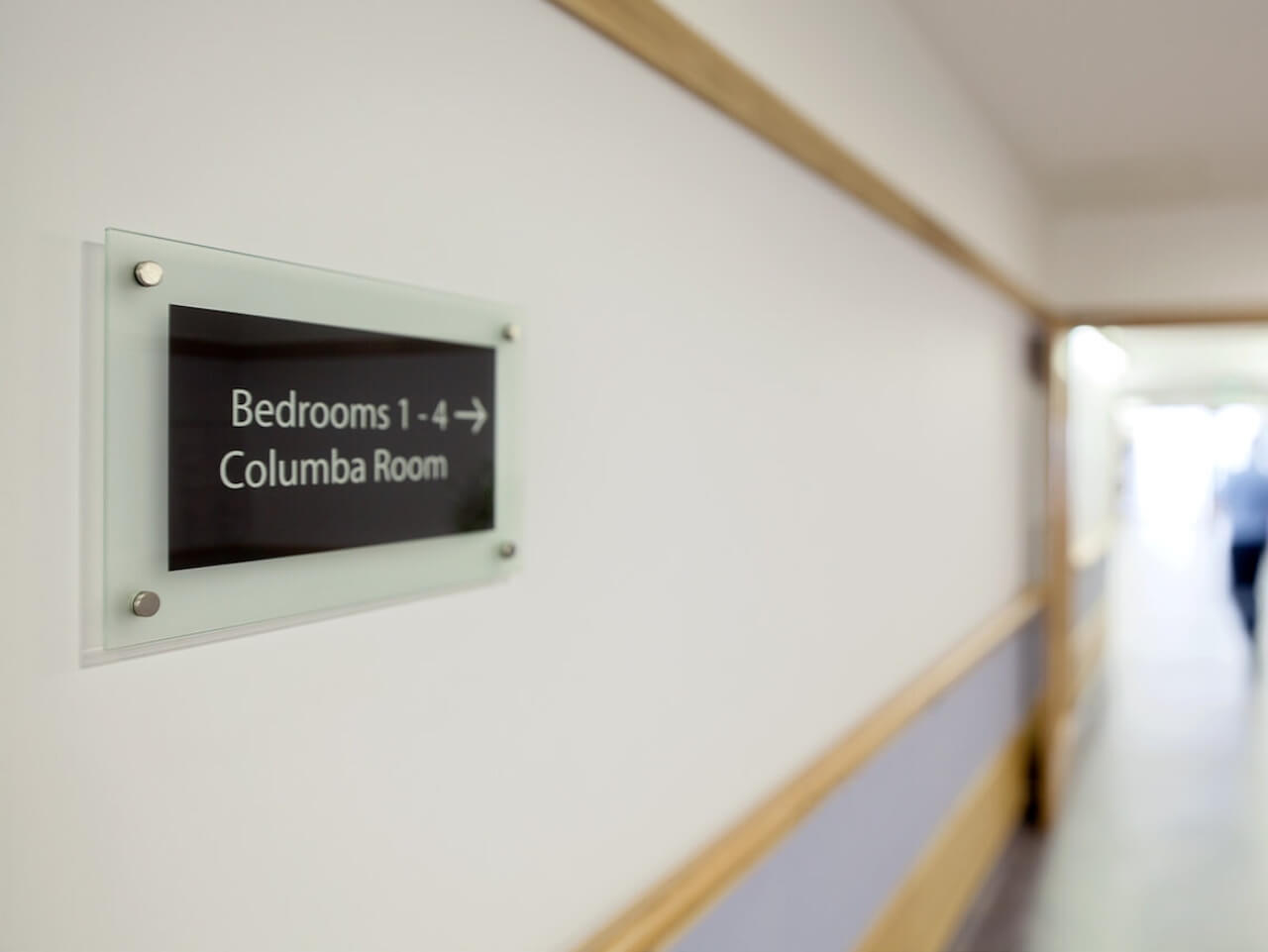 Wall mounted glass signage for bedrooms at St Columba's Hospice