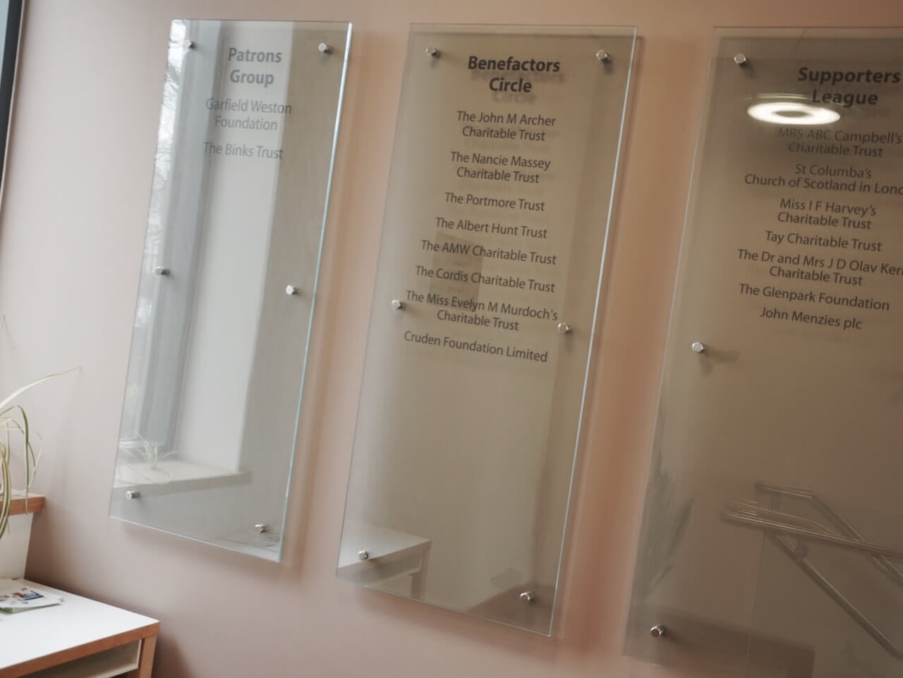 Etched glass benefactors boards on the wall at St Columba's Hospice