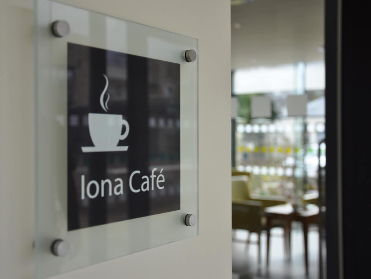 Glass mounted signage for the cafe with a pictogram of a coffee cup