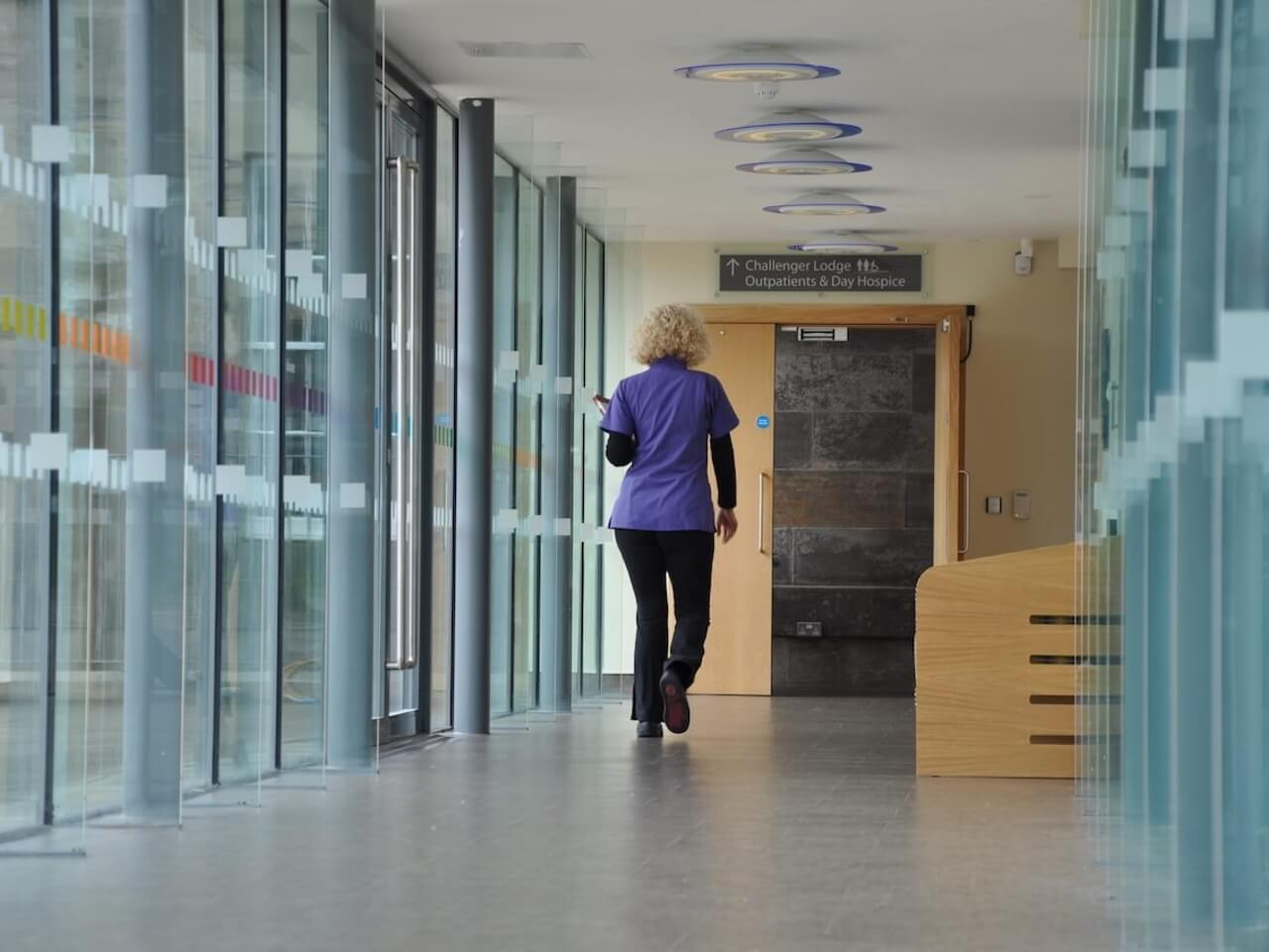 Healthcare signage and wayfinding with colourful manifestations along a glass corridor