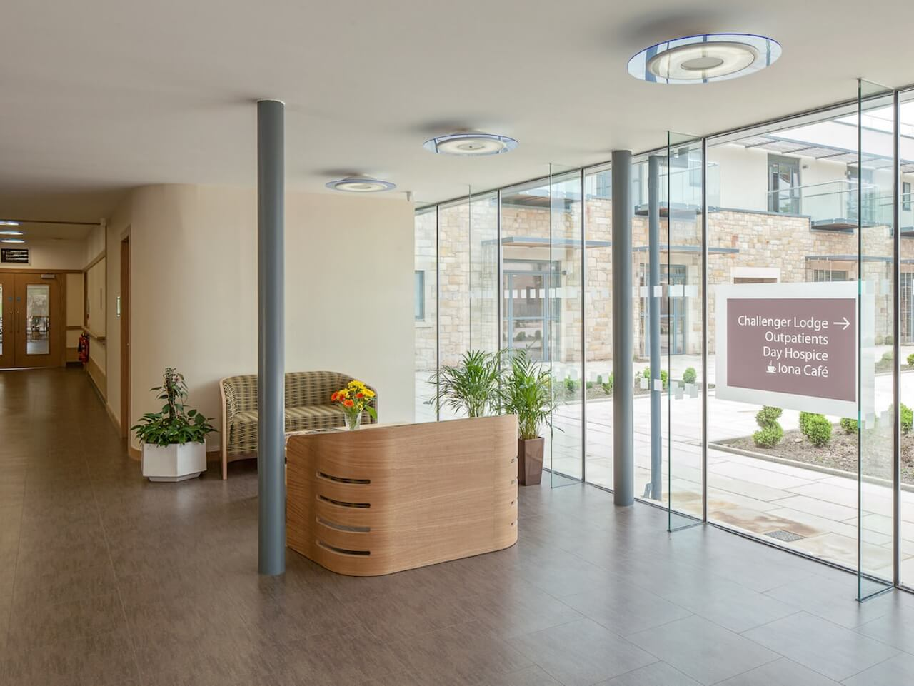 The entrance of St Columbas Hospice showing signage and etching on the glass walls to the outside