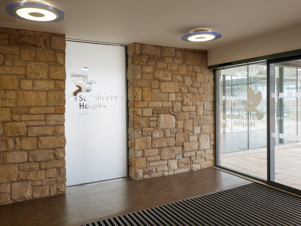 An internal glass partition with frosting and the St Columbas Hospice logo etched into it