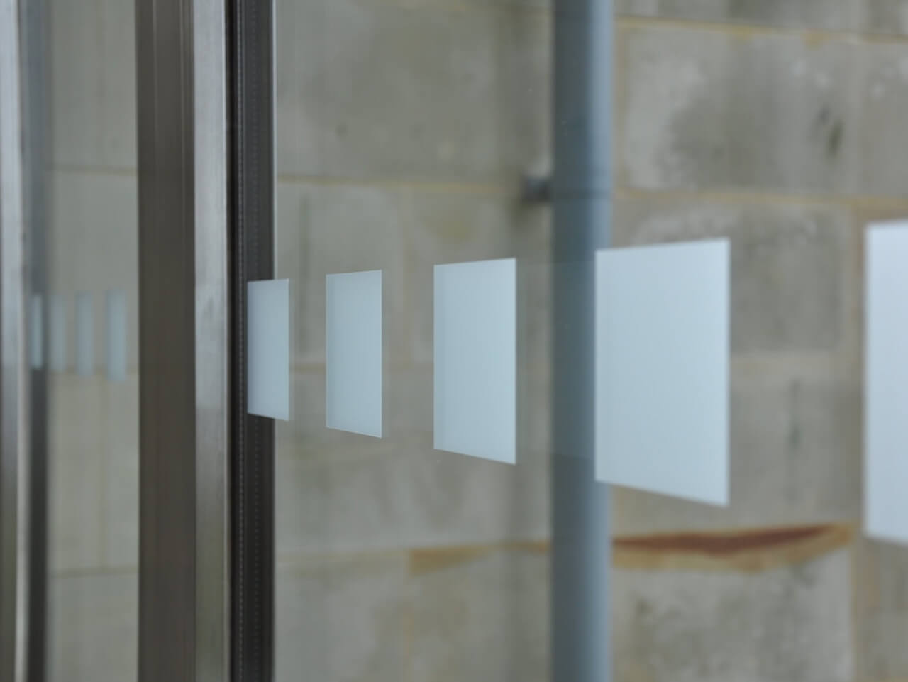 Frosted squre window manifestations on full size window panels at St Columba's Hospice