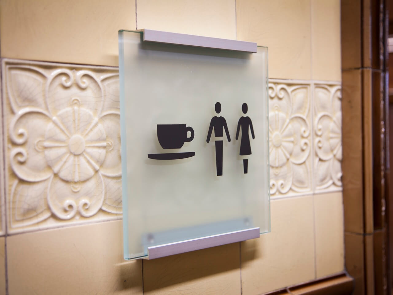 A glass wayfinding sign on the wall with logos for the cafe and the bathrooms