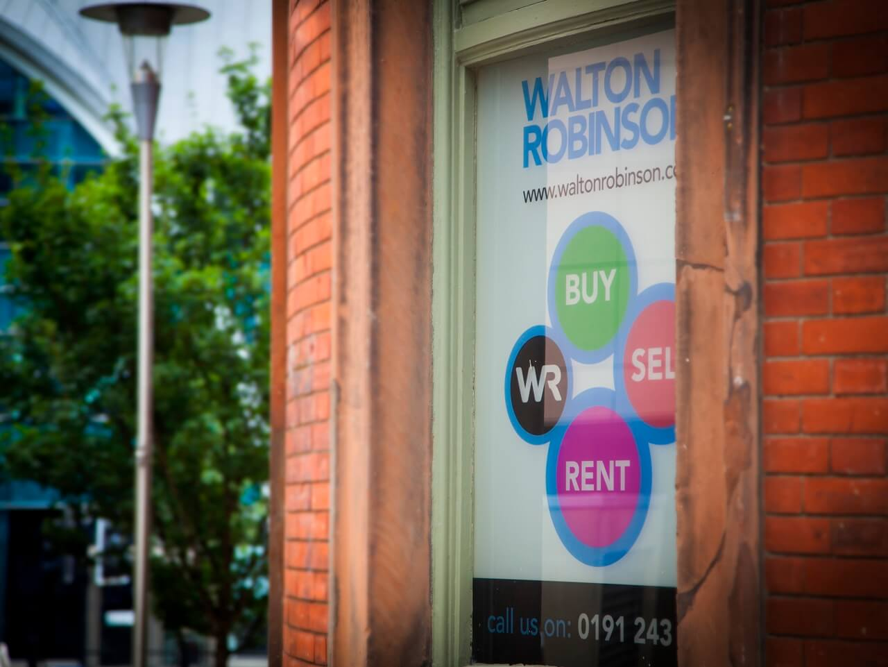 A Walton Robinson services poster displayed in a window of the office