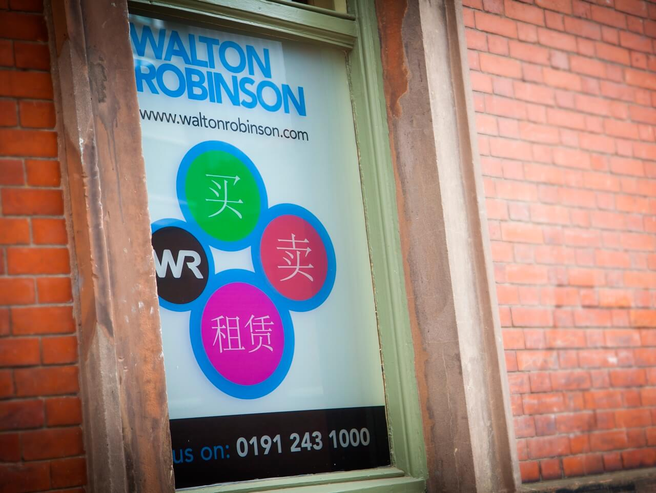 A Walton Robinson services poster in a window of the office